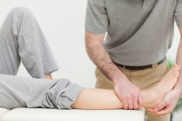 明るい部屋で女性の足を診察する医者に閉じなさい