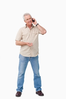 彼の携帯電話の上の成熟した男性