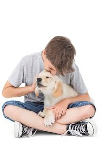 白い背景の上に子犬をキスしている少年