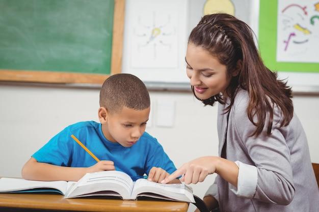 Довольно учитель помогает ученику за своим столом