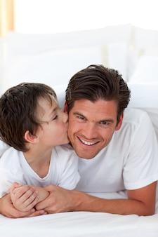 ベッドに横たわっている父親にキスをしている小さな男の子