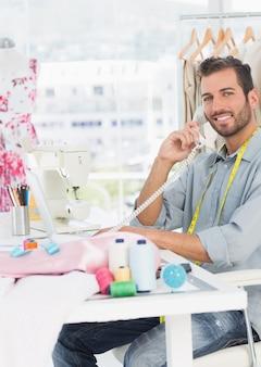 スタジオで電話を使用している若い男性ファッションデザイナーの側面の肖像画
