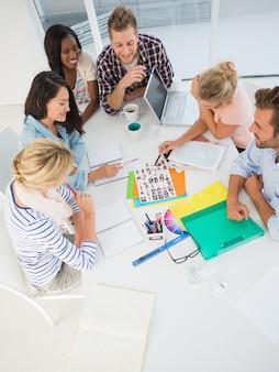 Молодая команда дизайнеров перебирает контактные листы вместе в креативном офисе