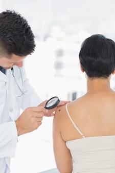 クリニックで虫眼鏡を持つ女性のモルを調べる皮膚科医