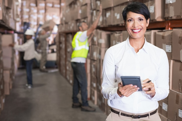 大きな倉庫で計算機を使用しているかなり倉庫マネージャー