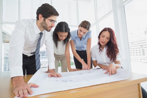 ビジネスチームは仕事の計画をオフィスで読む