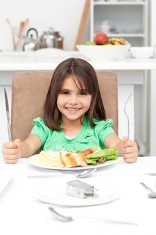 パスタとサラダを食べるためにフォークを持って愛らしい小さな女の子