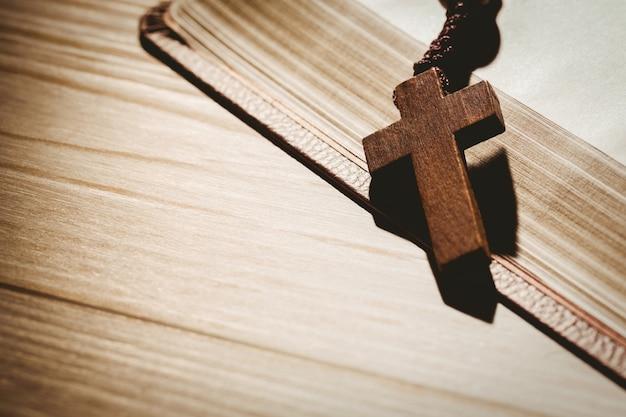 Открытая библия и деревянные четки