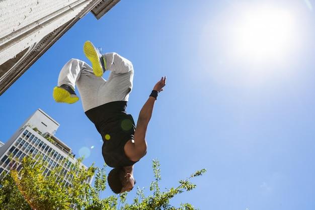 都市の建物の前で空中に飛ぶエクストリームアスリート