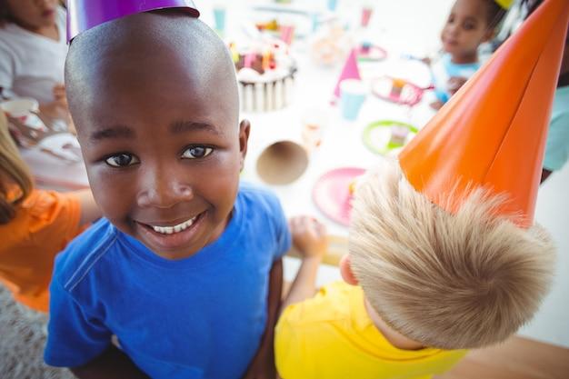 Возбужденный ребенок, наслаждающийся вечеринкой по случаю дня рождения, глядя на камеру