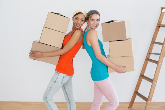 Женщины-друзья, движущиеся вместе в новом доме