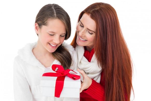 母と娘、白い背景にクリスマスプレゼントを開く