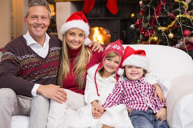 リビングルームで自宅でクリスマスの時間にソファに座って笑顔の家族の肖像画