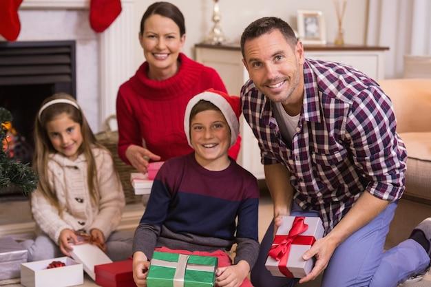 リビングルームで自宅でクリスマスを祝う笑顔の家族の肖像画