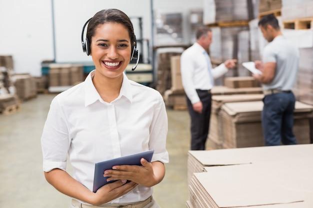 大きな倉庫でクリップボードを保持しているヘッドセットを着ている倉庫管理者