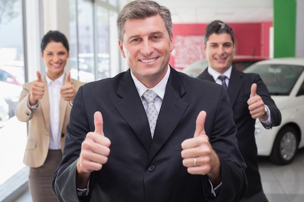 新しい車のショールームで親指をあげている間に立っている笑顔のビジネスチーム