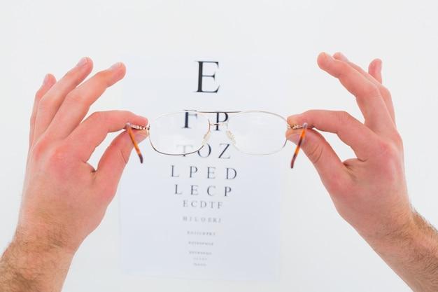白い背景に目のテストのための眼鏡を手に手