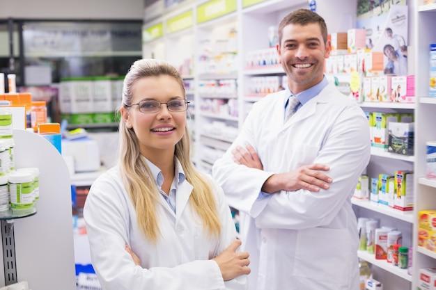 病院の薬局でカメラで笑っている薬剤師のチーム