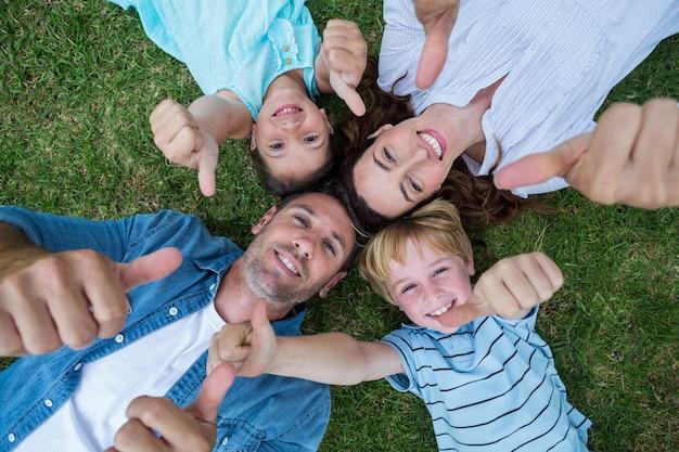 公園の幸せな家族は一緒に晴れた日に親指を上げる