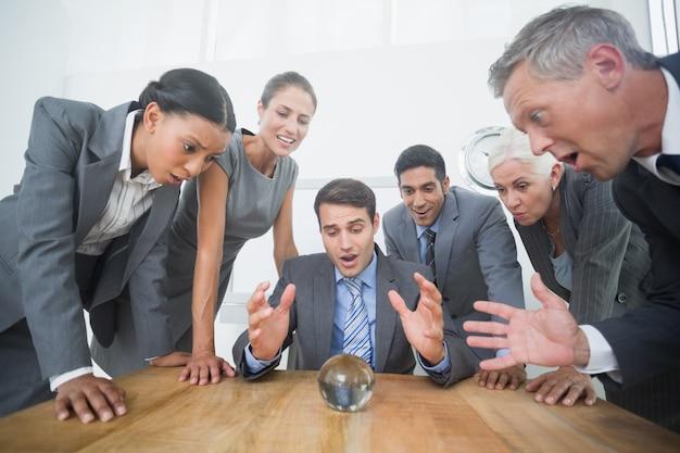 水晶球で未来を予測するビジネスマンのグループ