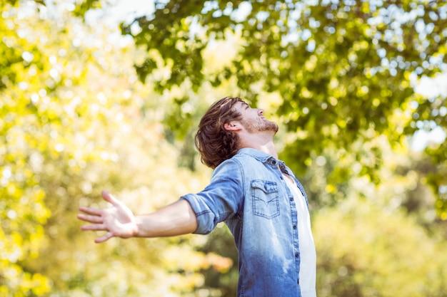 ハンサムなヒップスターは夏の日に公園で自由に感じる