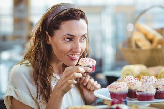 Довольно брюнетка, холдинг и пахнущий кекс в магазине хлебобулочных изделий