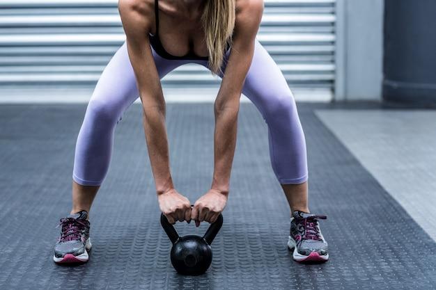 クロスフィットジムでケトルベルを持ち上げている筋肉の女性を尻目にする