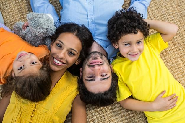 Улыбающаяся семья, лежащая на ковре и глядя на камеру