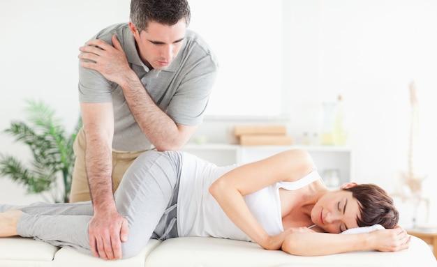 マッサージ師が女性の股関節をマッサージしています