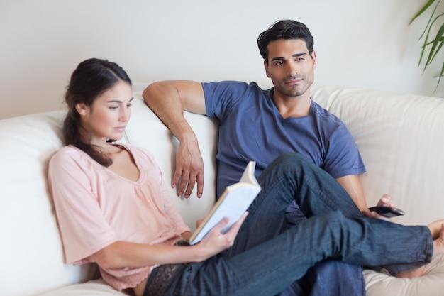 Женщина читает книгу, пока ее парень смотрит телевизор