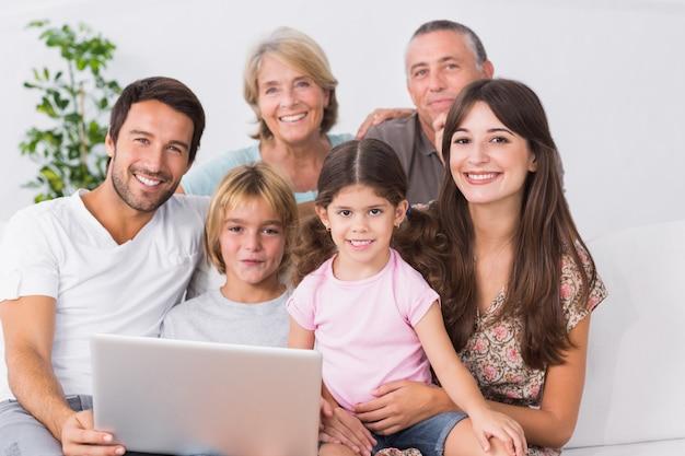 ラップトップを使用してソファで幸せな家族