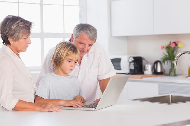 ラップトップを見る子供と祖父母