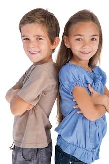 Дети, стоящие спиной к спине, скрестив руки