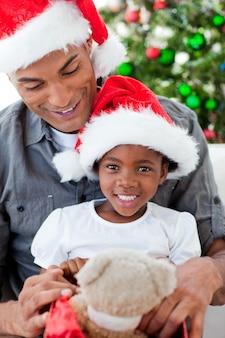 彼女の父親とクリスマスプレゼントで遊んでいる幸せな少女