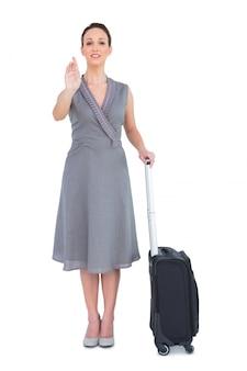 カメラに呼び出すスーツケース付きの陽気で豪華な女性