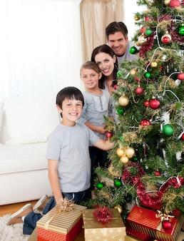 ブールとプレゼント付きクリスマスツリーを飾る幸せな家族