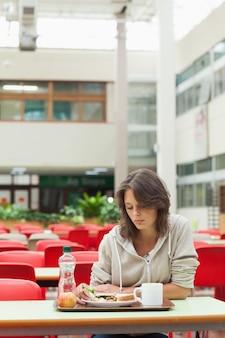 Грустный студент в столовой с подносом для еды