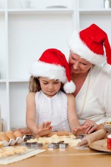 おばあちゃんとクリスマスケーキを焼く少女