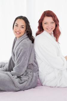 Женщины-друзья в халатах, сидящие спиной к спине на кровати