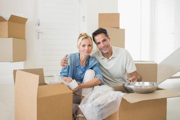 新しい家に箱を開けて笑うカップル