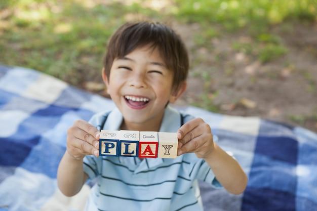 公園で遊ぶようなブロックアルファベットを保持している幸せな少年