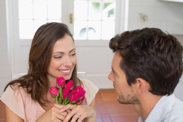 家で花を持つ男を見ている女性