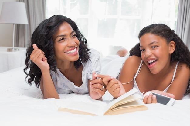 Мать и дочь читают книгу и слушают музыку вместе на кровати