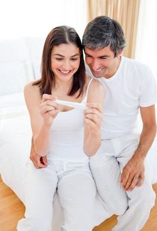 妊娠検査の結果を見つけている笑顔のカップル
