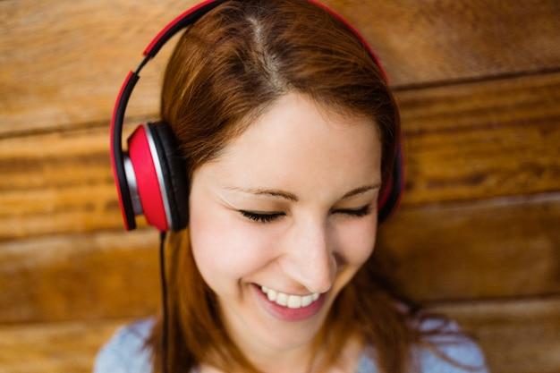 閉じた目で音楽を聴くナチュラル笑顔の赤毛