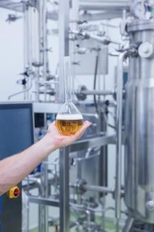 ビールのビーカーを示す手