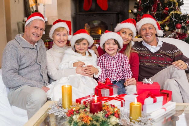 クリスマスの時間にカメラを見ている幸せな拡大家族