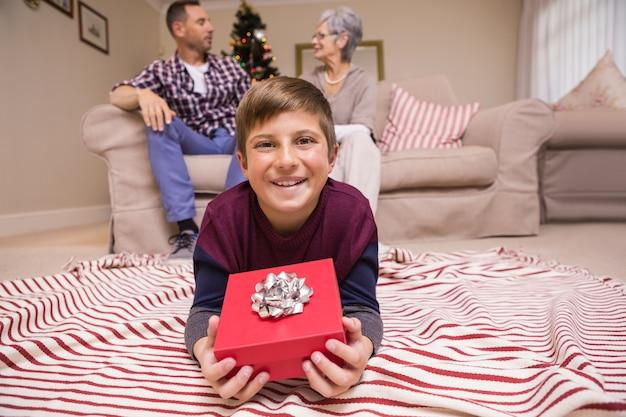 幸せな息子、彼の家族の後ろに贈り物を横たえ