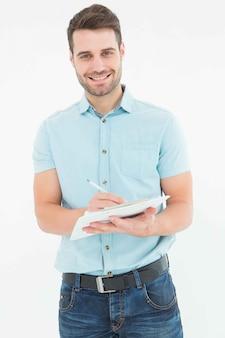 白い背景にクリップボードに書くハンサムな配達人の肖像