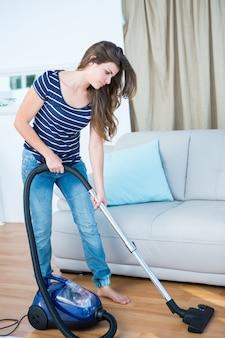 木製の床に掃除機を使用して女性